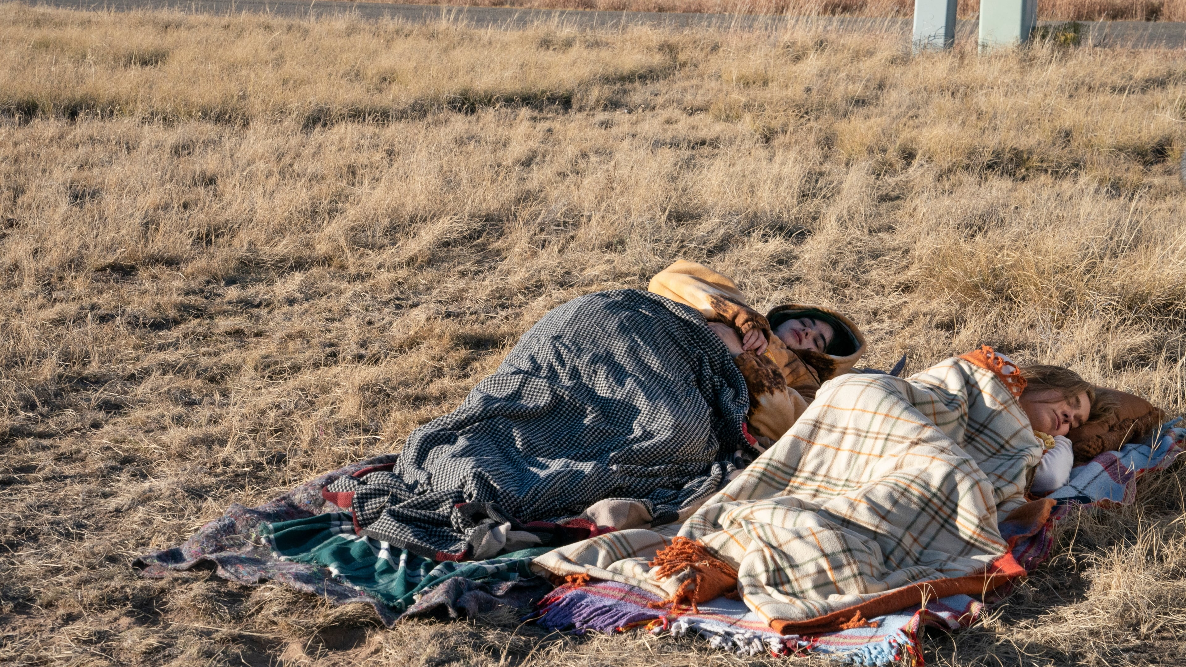 Bailey and Veronica lie side by side on the ground in a field of dry, yellow grass. They are sleeping wrapped in blankets and jumpers to protect them from the cold.